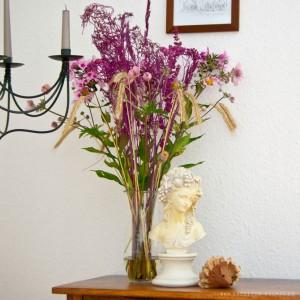 Fertige Vase mit frischen Blumen und farbigen Samenständen