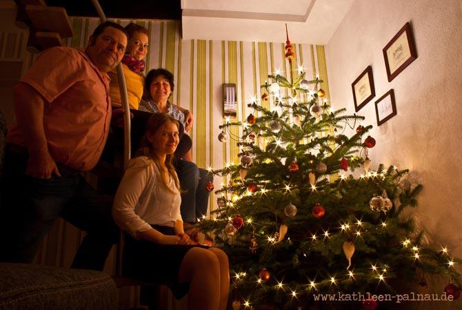 Familienfoto vor dem Weihnachtsbaum mit Bartmännchen